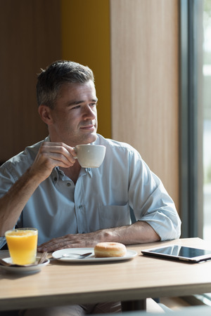 healthy looking: Businessman at the bar having a cup of coffee and looking through a window, healthy lifestyle concept Stock Photo