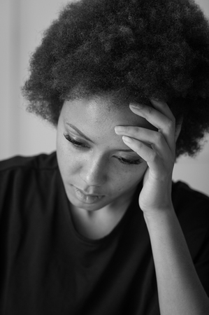 mujeres tristes: Sad african american woman touching her forehead and looking down, she is having an headache and feeling bad