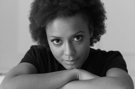 black girl: Confident young african american woman posing and looking at camera, she is leaning on her arms