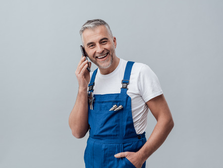 Confident repairman and plumber having a phone call with his smartphone and smiling