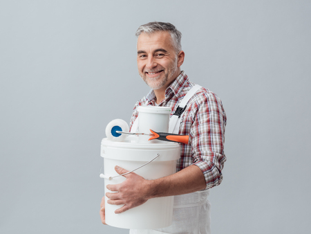 Smiling confident painter and decorator posing with a paint roller and buckets, he is looking at camera Stock Photo