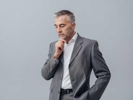 businessman thinking: Pensive businessman thinking with hand on chin, business strategies concept Stock Photo