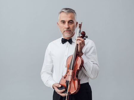 soloist: Confident mature musician posing with a violin and looking at camera, classical music and entertainment concept Stock Photo