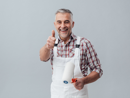 overalls: Cheerful painter and decorator giving a thumbs up, he is holding a paint roller Stock Photo