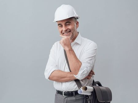 quantity: Confident construction engineer posing with hand on chin, he is smiling and carrying blueprints in a bag