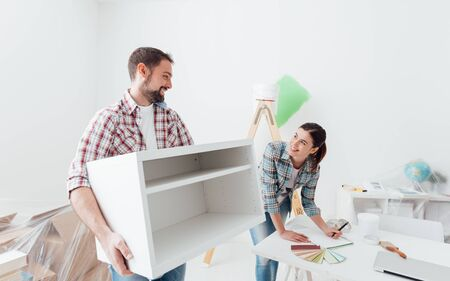 Young happy couple renovating their new house and moving furnishings together