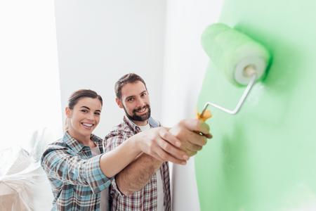 젊은 사랑하는 그들의 가정을 개조 부부, 그들은 벽 그림 및 페인트 롤러를 함께 들고