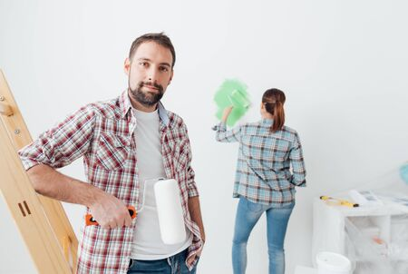 yourself: Home makeover and renovation: young couple redecorating their new house and painting walls, the man is leaning on a ladder and posing