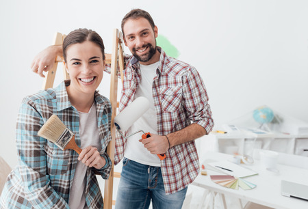 Un jeune couple créatif réhabilitant sa maison et ses murs de peinture, se posent ensemble et sourient à la caméra