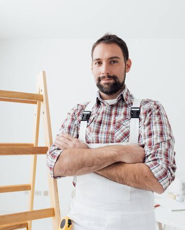 Confident professional painter posing with arms crossed, home renovation and decoration concept Stock Photo