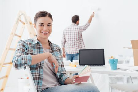 Young couple renovating their new house, the man is painting the wall with a paint roller and his girlfriend is holding color swatches and smiling at camera