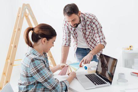 Jeune couple souriant rénovant leur maison, ils choisissent des échantillons de couleurs de peinture ensemble Banque d'images - 72066671
