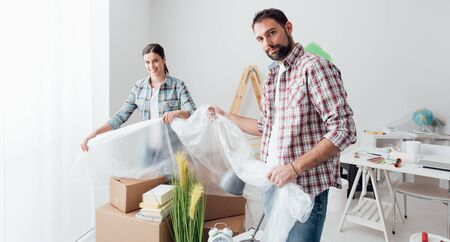 Two people preparing a room for painting, they are covering boxes and objects with a protective plastic sheet, home renovation concept