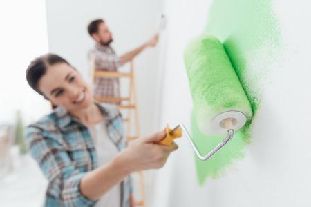 Pareja feliz pintura paredes en su nueva casa: el hombre está de pie en una escalera y la mujer está utilizando un rodillo de pintura y la aplicación de pintura verde brillante