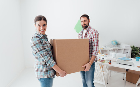 Young smiling couple moving into a new house, they are carrying full cardboard boxes Imagens