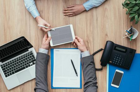 Mensen uit het bedrijfsleven ontmoeten elkaar op kantoor en gebruiken een digitale tablet; digitale handtekening, apps en online formulierenconcept Stockfoto