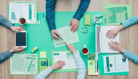 finance report: Business people working together on a green desktop and examining a report; environment, green business and finance concept Stock Photo