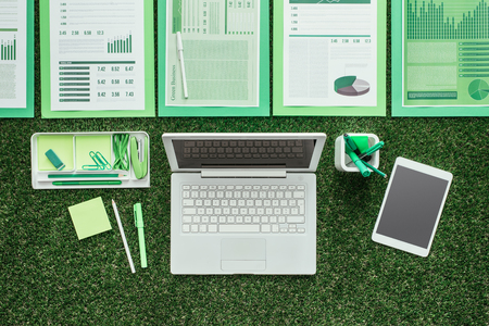 desk tidy: Laptop, tablet, office supplies and financial reports on the grass, green business and finance concept