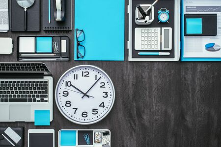 Corporate Business Desktop With Laptop, Office Accessories And A Clock:  Business Productivity And Deadlines