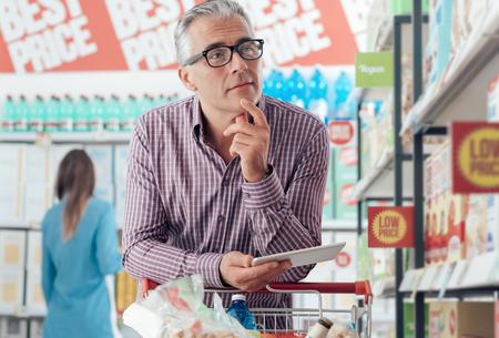 Homem confiável que faz compras de supermercado no supermercado, ele está à procura de produtos e ofertas que usam aplicativos em sua tabuleta digital