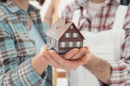 home loan: Man and woman holding a model house in their hands, real estate and construction concept