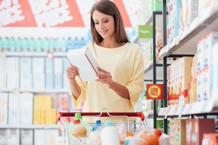 Young woman doing grocery shopping at the supermarket and reading food labels with ingredients on a box, shopping and nutrition concept Stock Photo
