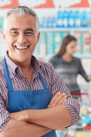 Confident smiling supermarket clerk posing at the shopping mall, retail job concept Stock Photo