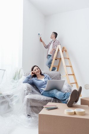 yourself: Happy couple doing home renovations, the man is painting the room and the woman is relaxing on the armchair and connecting with a laptop