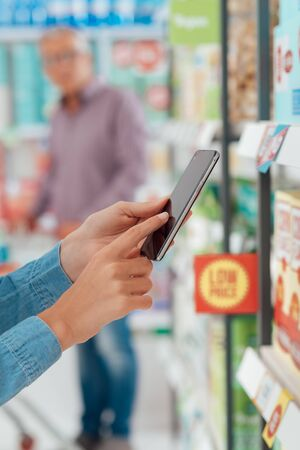 Woman shopping at the supermarket, she is checking products and offers using her smart phone, augmented reality and retail concept