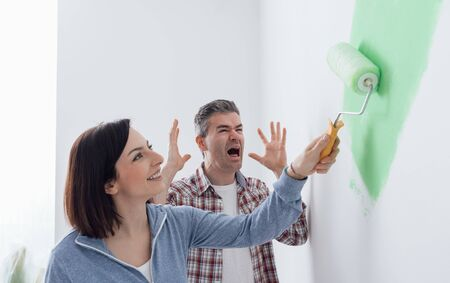 dislike it: Woman painting a room with bright green, her husband is desperate and screaming; home renovation and lifestyle concept