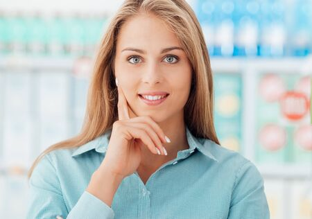 Young attractive woman shopping at the supermarket, she is smiling and posing with hand on chin, store shelves on the background Stock Photo
