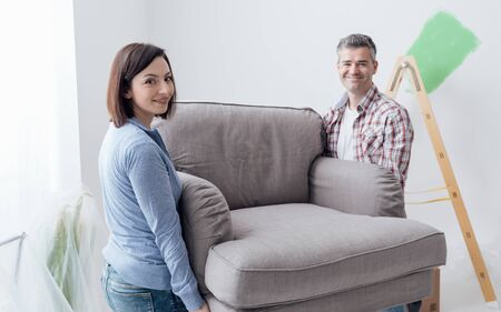redecoration: Couple moving furniture in their new house and doing home renovations, they are carrying an armchair