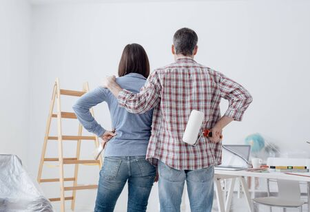Loving couple staring at their freshly painted room, back view: home renovation and relationships concept Stock Photo