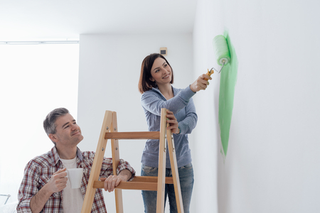 man painting: Happy couple doing a home makeover and painting walls, the woman is using a paint roller and the man is holding the ladder