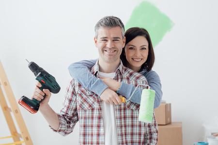 Lächelnde liebevolle Paare, die Haupterneuerungen tun, die Frau hält eine Farbenrolle und der Mann benutzt einen Bohrgerät