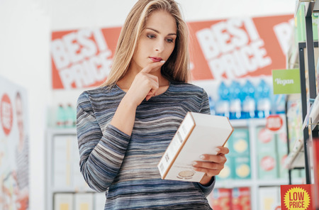 Young woman doing grocery shopping at the supermarket and reading a food label with ingredients on a box, shopping and nutrition concept