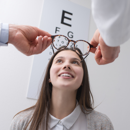 Young happy woman trying her new pair of glasses after the eye exam Stock Photo