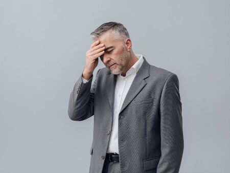 business problems: Exhausted businessman with headache, he is touching his forehead, business failure and problems concept Stock Photo