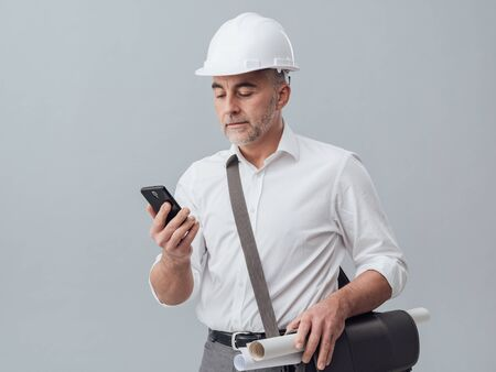 Construction engineer using a smartphone, he is connecting and text messaging Stock Photo