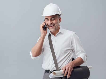 Construction engineer using a smartphone, he is having a phone call Stock Photo