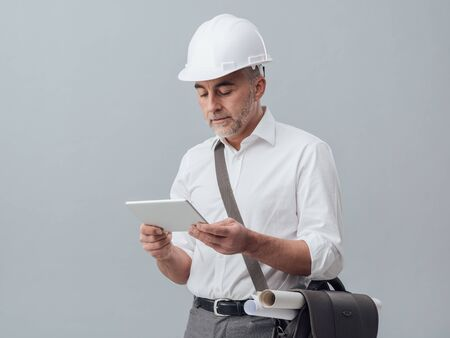 Construction engineer connecting with a digital tablet and using apps, he is wearing a safety helmet Stock Photo