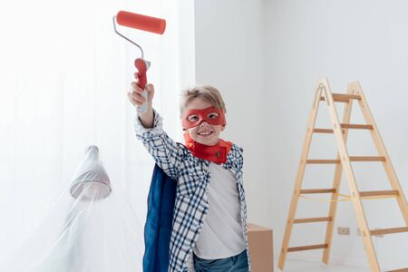 Cute superhero boy with mask and cape, he is holding a paint roller and smiling at camera, home renovation and diy concept Stock Photo