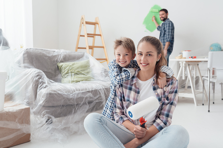 Home makeover, decoration and painting: a kid is smiling and posing with his mother and his father is painting with a roller on the background