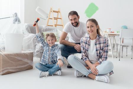 Home make-over, decoratie en schilderkunst: gelukkig gezin lacht en poseert, de jongen houdt een verfroller vast