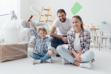 Home makeover, decoration and painting: happy family smiling and posing, the boy is holding a paint roller