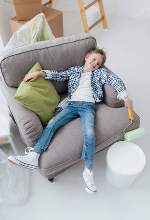 Lazy boy liying on the armchair and holding a paint roller, home renovation, decoration and improvement concept