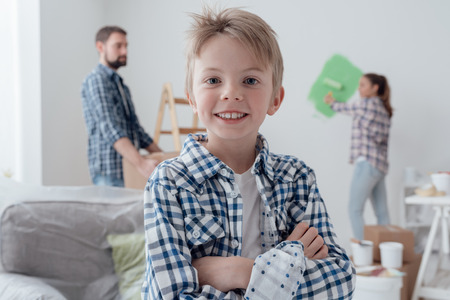 Home improvement and decoration concept: family painting a room and moving cardboard boxes, a cute confident boy is smiling on the foreground Stock Photo