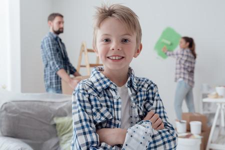 Huisverbetering en decoratie concept: familie schilderij een kamer en bewegende kartonnen dozen, een schattige zelfverzekerde jongen lacht op de voorgrond Stockfoto
