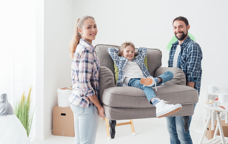 furnishings: Happy young family moving into a new home, a man and a woman are carrying a new armchair and their son is sitting on it