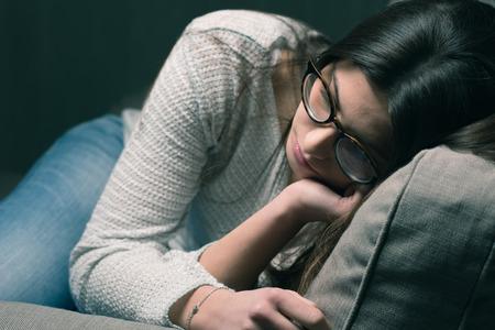 Sad jonge vrouw met een bril zitten op de bank thuis, ze is depressief en eenzaam Stockfoto